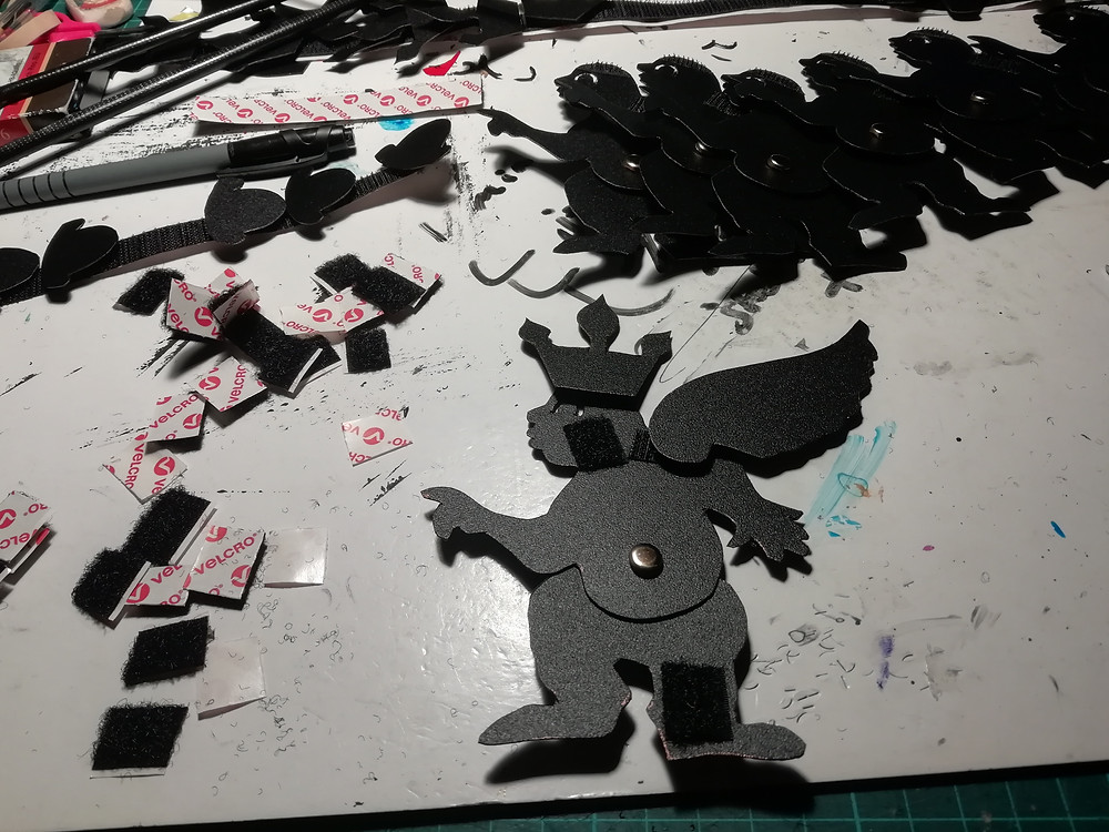 Black shadow puppets are being cut out on the puppet makers workshop station. There are lot's of velcro pieces lying around ready to attach the puppets to sticks.