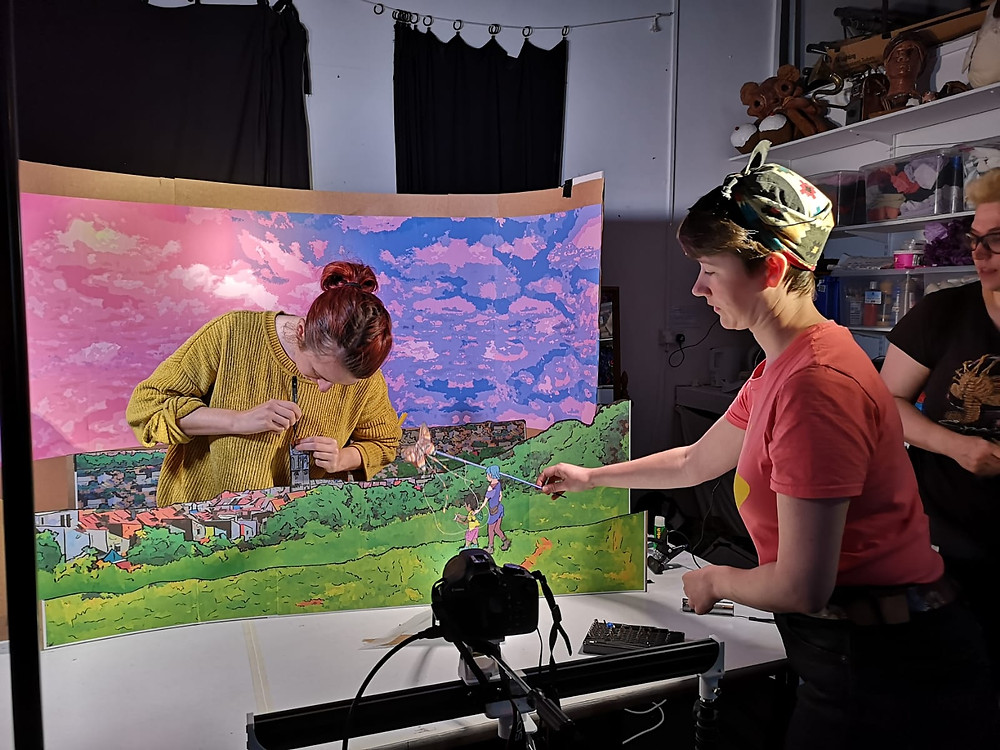 Three white artists work on a set for a puppet film. A camera sits in the foreground facing the sceve. A paper-cut countryside scene sits in the middle ground with a pink and blue painted sky in the background.