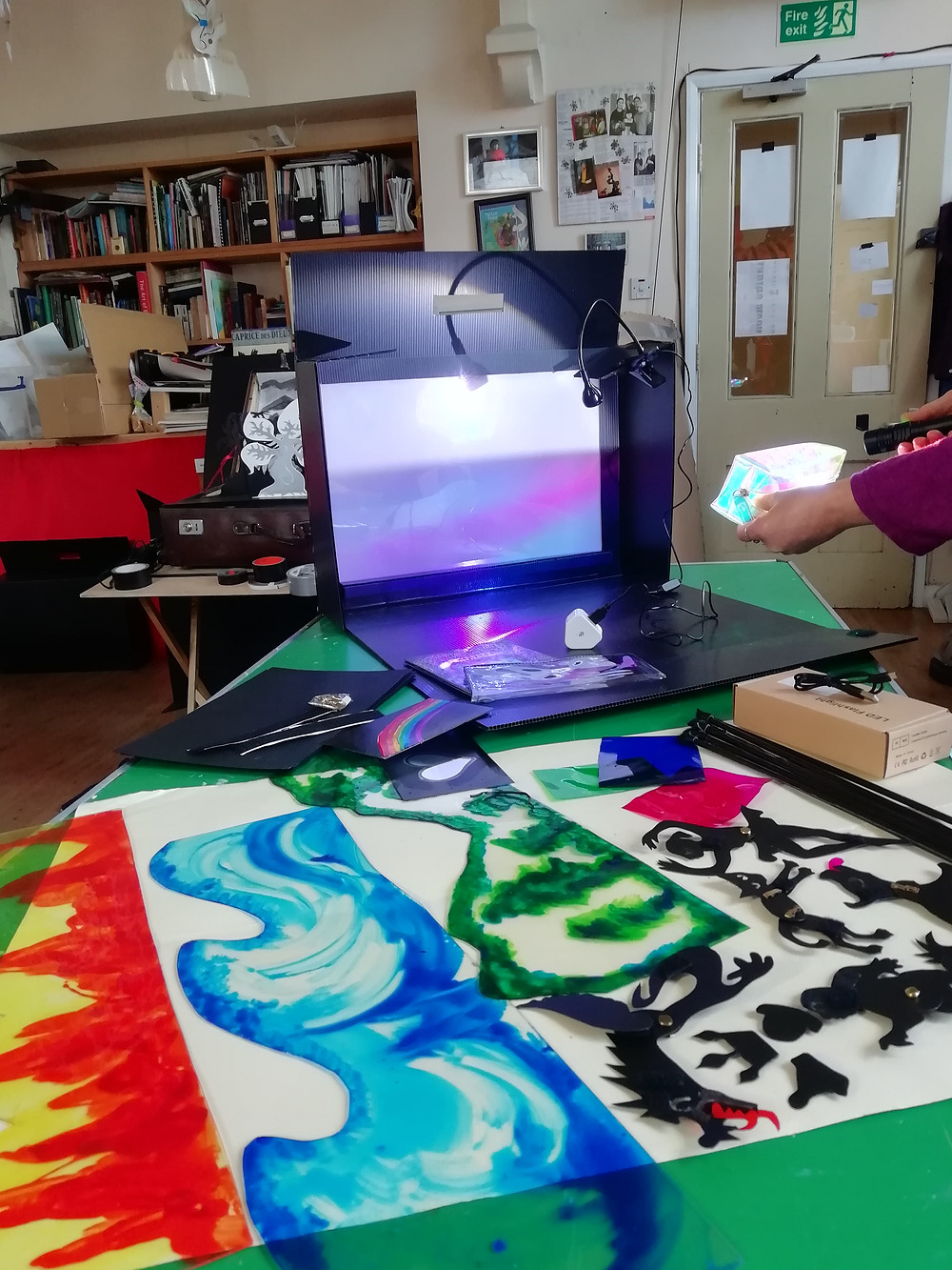 The shadow puppet kit with all of the contents is laid out on a green table. The shadow screen box with a light has puppets and coloured backgrounds placed in front of it ready for use. A puppeteer holds one of the backgrounds in front of the light source to demonstrate the effect on the screen.