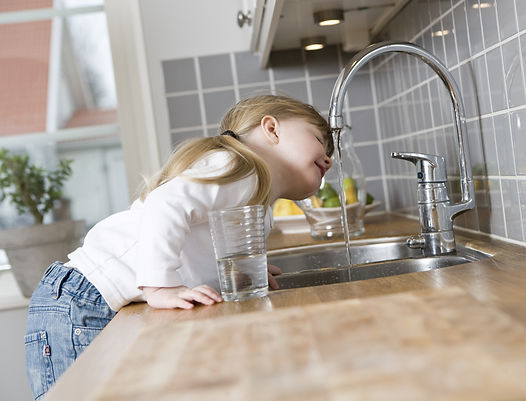 Kleines Mädchen trink Wasser aus Wasserhahn