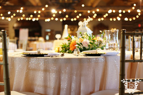 Dining Tables: Peach Polyester with French Lace table Runners Head Table: Ice Peach Polyester with Glitz and Glimmer in Blush Gold Chargers White Cotton Napkins with Pearl and Diamond Napkin Rings Floral by Mary Murrays Photo Credit: Sarah Baker Photos   https://sarahbakerphotos.shootproof.com/