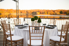 Dining Table Linen: Tone-on-tone White  Napkins: Black  Chargers: Gold Centerpieces: mini-boxwoo topiaries Photo Credit: Ace Cuervo