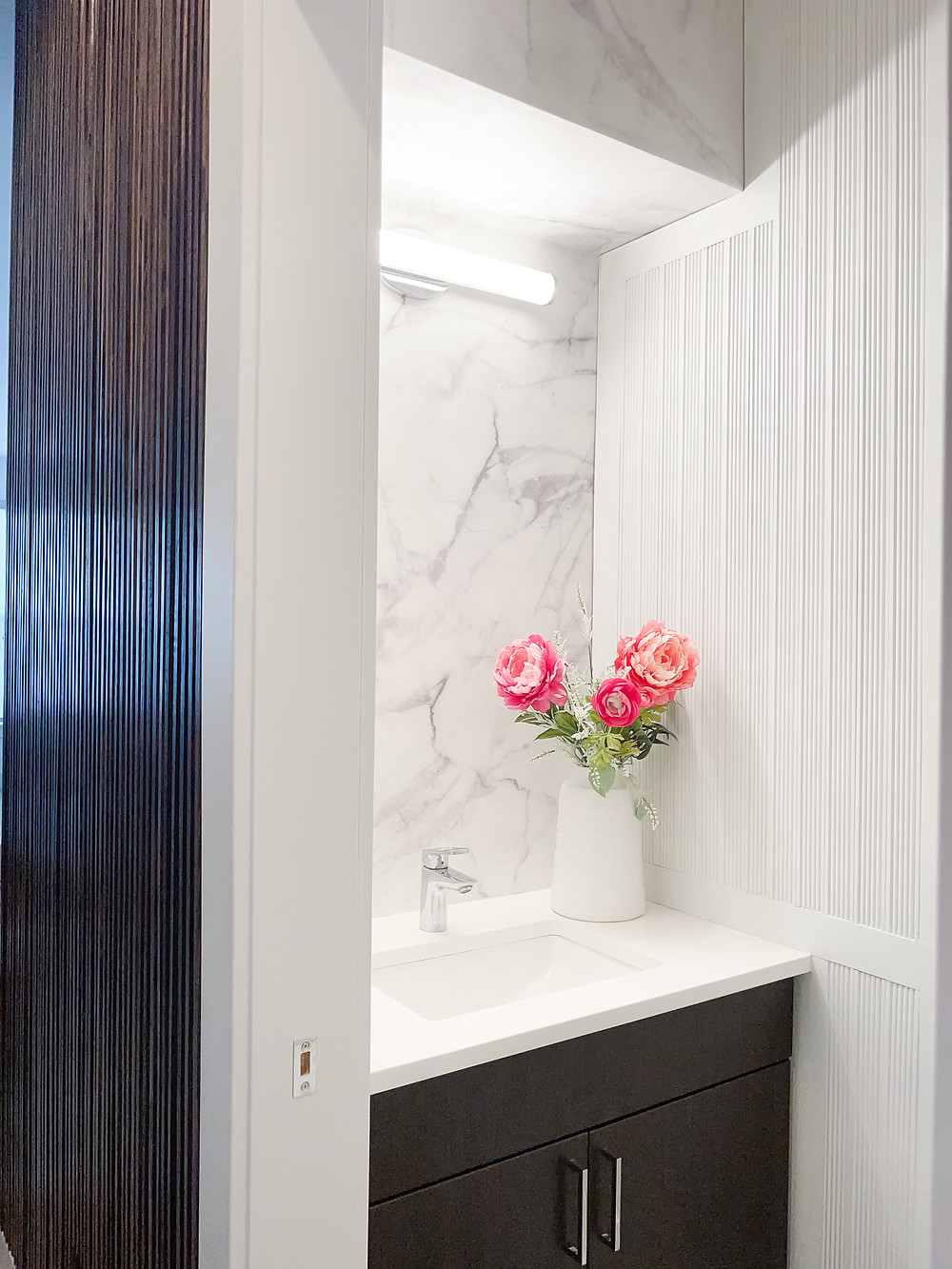 Modern Powder Room Reveal with a fluted accent wall, marble wallpaper and gray paint to create the perfect bathroom oasis. A stunning DIY powder room makeover with beautiful millwork.