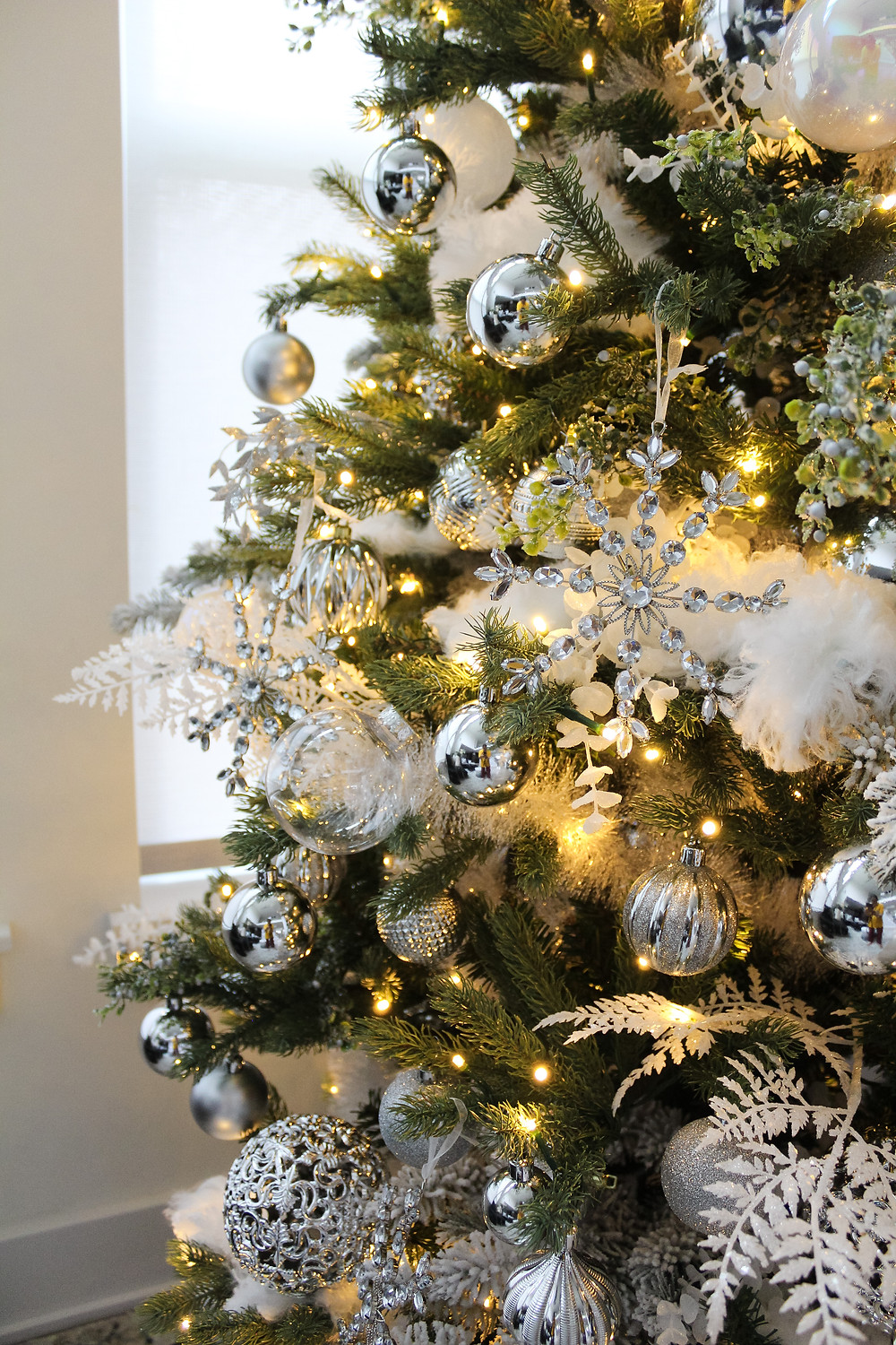 Create a stunning white snowcapped Christmas tree filled with clear, white and silver ornaments. Use white fern and eucalyptus stems and finish this tree off with snowflake ornaments. You are on your way to a White Christmas with this gorgeous modern tree! #christmasdecor #holidaydecor #whitechristmas