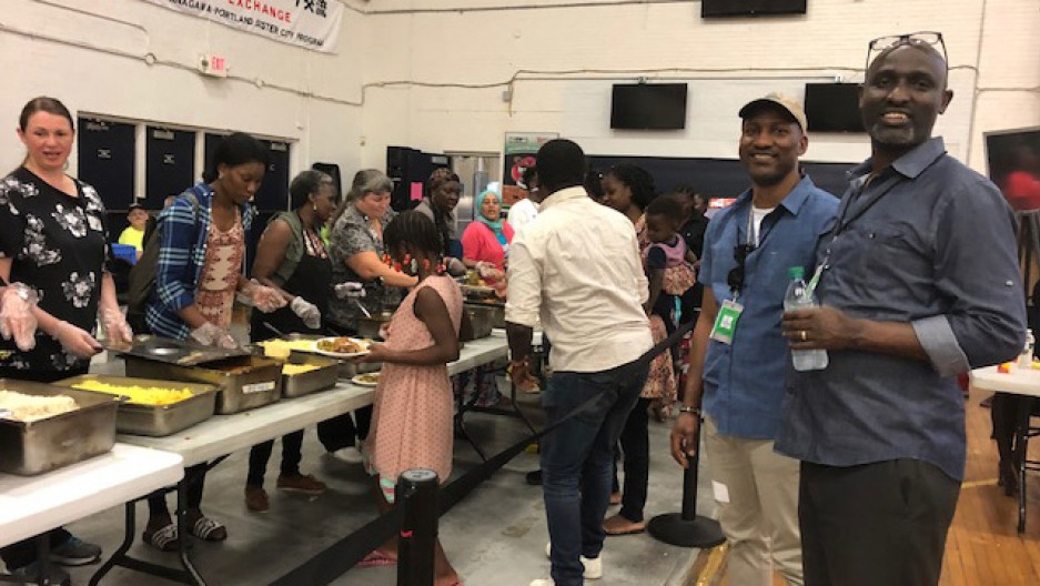 Two black men smile at the camera. They are standing in an a crowded, open gymnasium, behind them volunteers of many races and cultures serve a homecooked meal to families and children seeking asylum