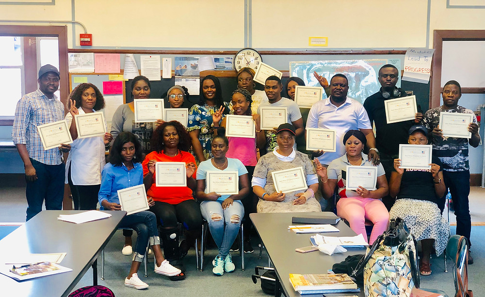 A classroom of smiling adults holding certificates of course completion. They are recent immigrants from central africa.  Posing in a group in front of an old-fashioned blackboard, they smile, wave and make peace signs at the camera to show pride in their accomplishment.