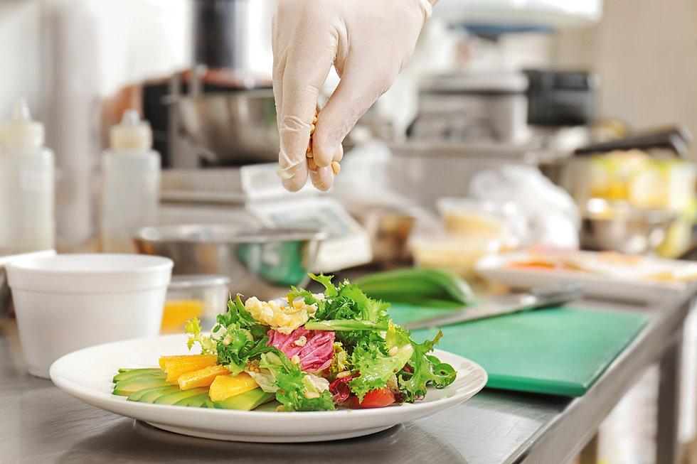 Female chef decorating delicious salad o