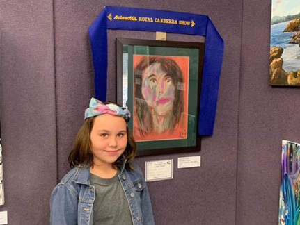 Evie standing next to her prize winning portrait.