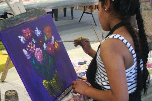 An art student painting a vase of flowers at Lavender Art Studios