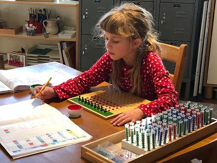 Montessori Elementary Child using materi