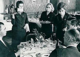 National Hotel restaurant, Moscow. Waitresses serve foreign tourists in gauze medical masks as a precaution against Hong Kong flu, USSR, 1969