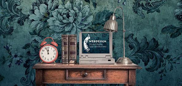 Schreibtisch mit Uhr, Laptop und Lampe.