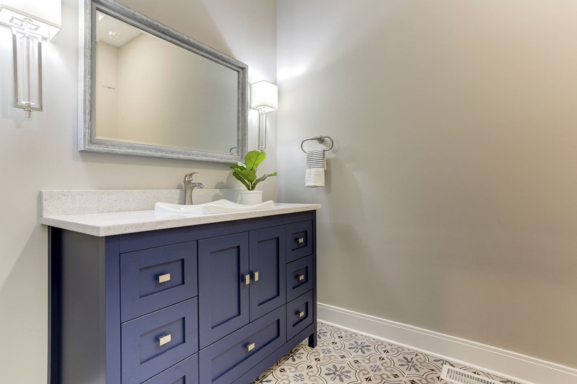 Bathroom vanity in blue with floor tile that demands attention