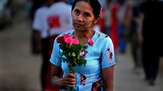 A supporters holding flowers wait for the arrival of Myanmar's pro-democracy leader Aung San Suu Kyi, in the village of Wah Thin Kha a day before the country's by-elections in the Myanmar.