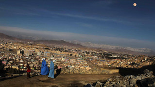 Afghan women walk along a road leading to a hilltop as a portion of Kabul city is seen in the background in Kabul, Afghanistan,  2010.