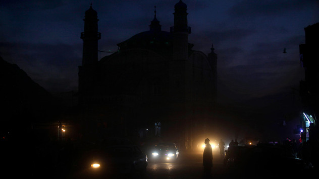 An Afghan man waits for transport as night falls in Kabul, Afghanistan, 2010.