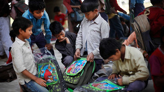 Underprivileged boys look at their new school bags, donated by a philanthropist, at free school run under a metro bridge in New Delhi, India, Mar. 19, 2013.