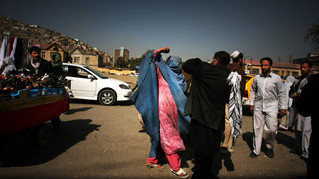 An agitated Afghan woman punches a man after he allegedly misbehaved with her at a market place in Kabul, Afghanistan, 2009.