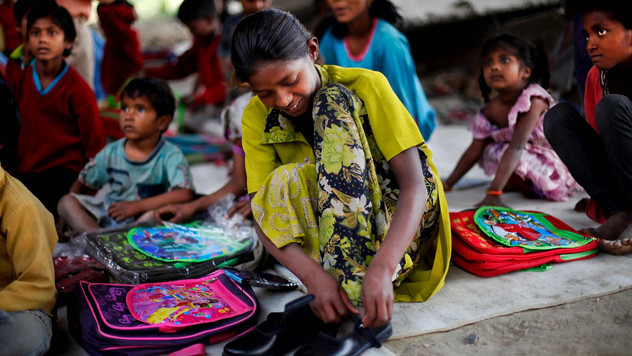 An underprivileged girl tries her new pair of shoes, donated by a philanthropist, at free school run under a metro bridge in New Delhi, India, Mar. 19, 2013.