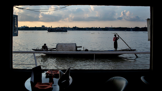 A fisherman boat moves past a floating hotel on the river Hooghly, a distributary of the river Ganges, in Kolkata, in the eastern Indian state of West Bengal, Friday, Oct. 11, 2019. Once the capital of the British raj, today the seething metropolis is home to nearly 15 million people. The Hooghly is also known as the Ganga by locals.