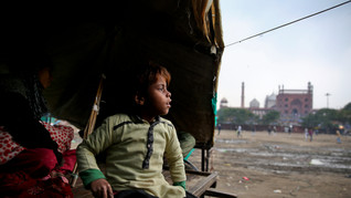 7-year-old Farmaan looks out from his home, set up on a wooden fruit vendor's cart, as it drizzles in New Delhi, India.
