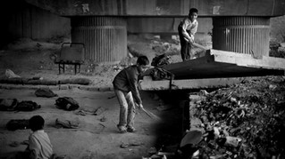 Underprivileged Indian children clean a portion of a free school run under a metro bridge, which they attend, before the commencement of routine classes in New Delhi, India, Wednesday, Nov. 7, 2012.