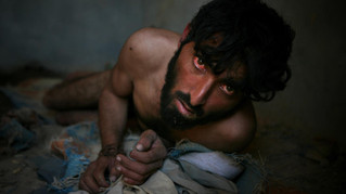An Afghan opium addict, who has lost his mental balance, looks on as he is chained to the wall at the Mia Ali Baba Shrine, on the outskirts of Jalalabad.