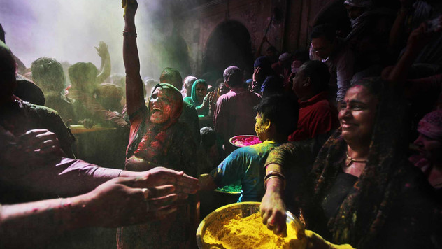 Hindu devotees throw colored powder on each other inside Banke Bihari temple during Holi festival celebrations in Vrindavan, India.