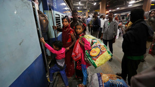 Marjina and her daughter Murshida, 12, and seven-year old son Shahid-ul board a train at a railway station in New Delhi, India.