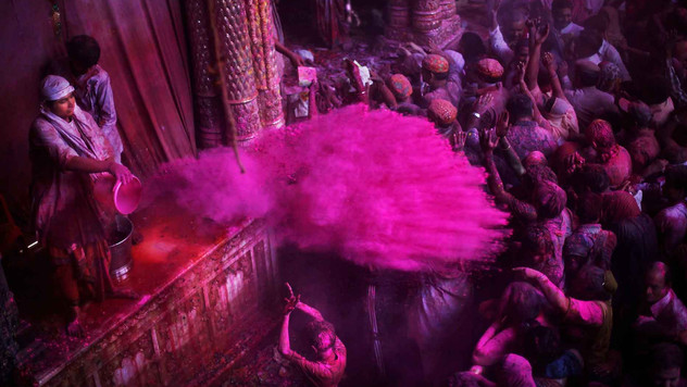 A young Hindu priest throws colored powder on devotees inside Banke Bihari temple during Holi festival celebrations in Vrindavan, India.