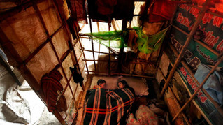 Murshida, 12, right, looks at her brother Shahid-ul, 7, lying ill on the floor inside their rented shanty on the outskirts of New Delhi, India, Nov. 10, 2014.