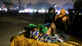 7-year-old Farmaan falls asleep while attending to his 3-month-old sister Razia, on a hand cart, which is their family's home, in New Delhi, India.