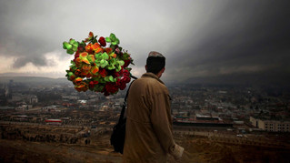 Hikmat, an Afghan street photographer holds artificial flowers while waiting for customers on a hilltop on a rainy day in Kabul, Afghanistan, 2010.
