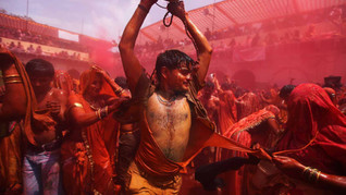 Indian Hindu women playfully tear the clothes of a man during celebrations marking Holi, the Hindu festival of colors, at the Dauji Temple.