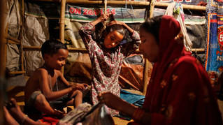 Marjina sews the torn shirt of her son Shahid-ul, 7, as her daughter Murshida, 12, combs her hair inside their rented shanty on the outskirts of New Delhi, India, Nov. 6, 2014.