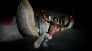 Mohammad, an inmate of Drug Treatment and Rehabilitation Center kicks a punching bag as he works out in Kabul.