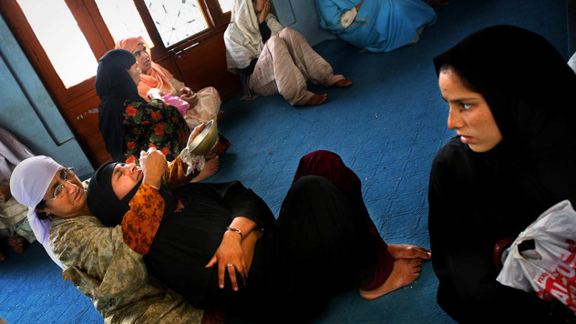 A Kashmiri muslim woman with an acute stomach ache is comforted by her mother (L) inside a shrine in Srinagar, the summer capital India-administered Kashmir, 2007.
