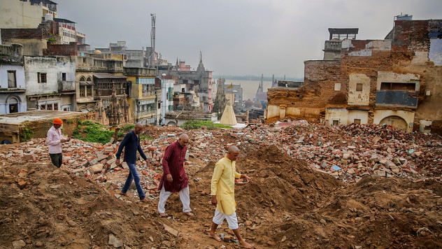People walk past demolished buildings at the site of a proposed grand promenade connecting the river Ganges with a centuries-old temple dedicated to Lord Shiva, in Varanasi, one of the Hinduism's holiest cities, in the northern Indian state of Uttar Pradesh, India, Monday, September 23, 2019.