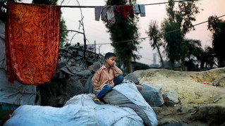 Shahid-ul, 7, sits on a sack of trash outside a shanty where he lives with his mother Marjina and sister Murshida, 12, on the outskirts of New Delhi, India.