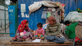 Ruby Khan, left, and Nisar Khan help their 7-year-old son Farmaan with his homework as they sit on a wooden fruit vendor's cart, which is their home, in New Delhi, India.