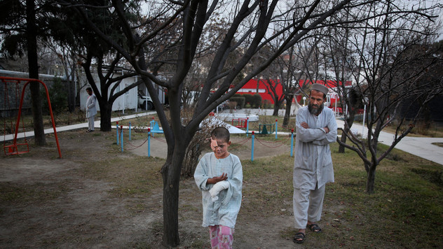 Ismatullah follows his nine-year-old son Eimal, who has lost his right eye and several fingers on his hands in a landmine blast, as he tries to walk in the compound of Emergency Surgical Center for Civilian War Victims in Kabul, Afghanistan, Thursday, Dec. 12, 2019.