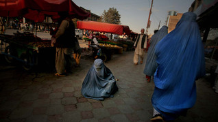 An Afghan woman ask for alms as she sits on a footpath at a marketplace in Kabul, Afghanistan, 2009.