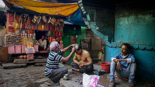 A barber tonsures a Hindu man as he prepares to participate in cremation rituals at Manikarnika Ghat, one of the oldest and most sacred place for Hindus for cremation on the banks of river Ganges in Varanasi, in the northern Indian state of Uttar Pradesh, Friday, March 22, 2019. For millions of Hindus, Varanasi is a place of pilgrimage and anyone who dies in the city or is cremated on its ghats is believed to attain salvation and freed from the cycle of birth and death.