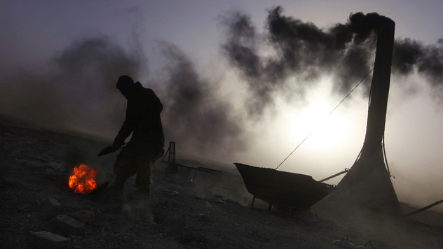 An Afghan worker adds coal into the furnace at a brick kiln on the outskirts of Kabul, Afghanistan, 2010.  An average worker can earn US$ 200 to US$ 300 a month.