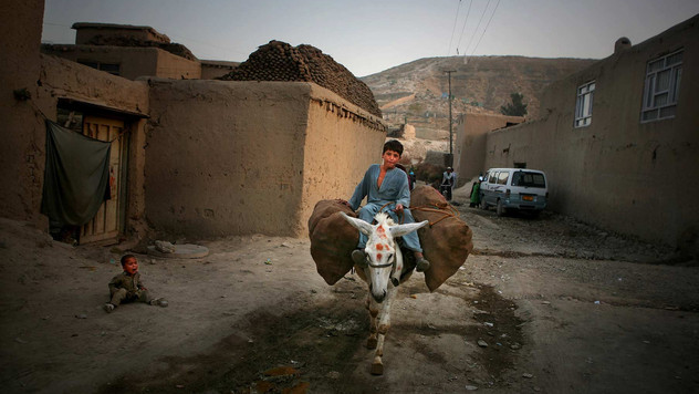 An Afghan boy rides his donkey as a child cries outside his home in Kabul, Afghanistan, 2009.