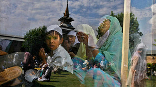 Tomb of Kashmir's Grand Mosque is reflected on the glass windows as Kashmiri Muslims during the second Friday of the holy month of Ramadan in Srinagar, the summer capital of India-administered Kashmir, 2007.