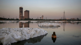 Chemical foam caused by industrial and domestic pollution is seen flowing towards a figurine stuck in the shallow waters of Yamuna river in New Delhi, India, Saturday, Oct. 8, 2019. Despite the river being accorded the status of a living human entity by an Indian court, untreated sewage and industrial pollutants have turned it into one of the most polluted rivers in the world. The river Yamuna is one of the major tributaries of the Ganges.