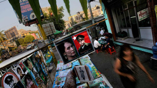 Pedestrians walk past a roadside stall selling the posters of Myanmar's democracy icon Aung San Suu Kyi and her late father Gen. Aung San at a market place in Yangon, Myanmar.