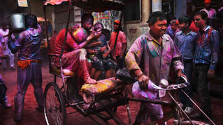 A woman, drenched in colored water, covers the face of a child as they ride a rickshaw past people celebrating Holi festival outside Banke Bihari temple in Vrindavan.