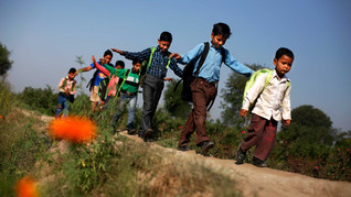 Underprivileged Indian boys, wearing new shoes, walk through a field on their way to a free school run under a metro bridge in New Delhi, India, Apr. 5, 2013.